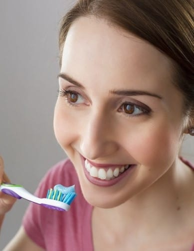 Ragazza che si lava i denti con dentifricio all'aloe vera