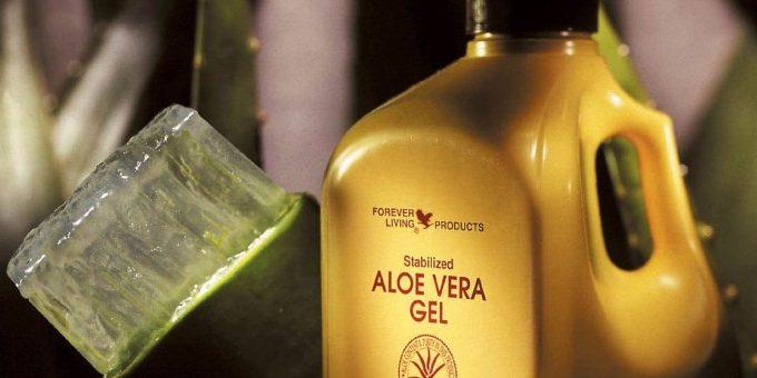 Bottiglia di aloe vera gel da bere della Forever Living con una foglia di aloe accanto
