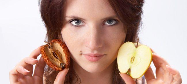 Ragazza che mostra l'invecchiamento della pelle con 2 mele