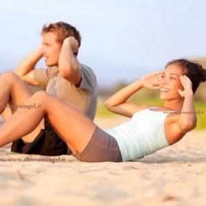 Coppia di ragazzi che fanno addominali in spiaggia
